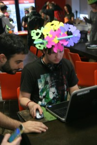 A man at a computer wearing an intricate crown made of many colors